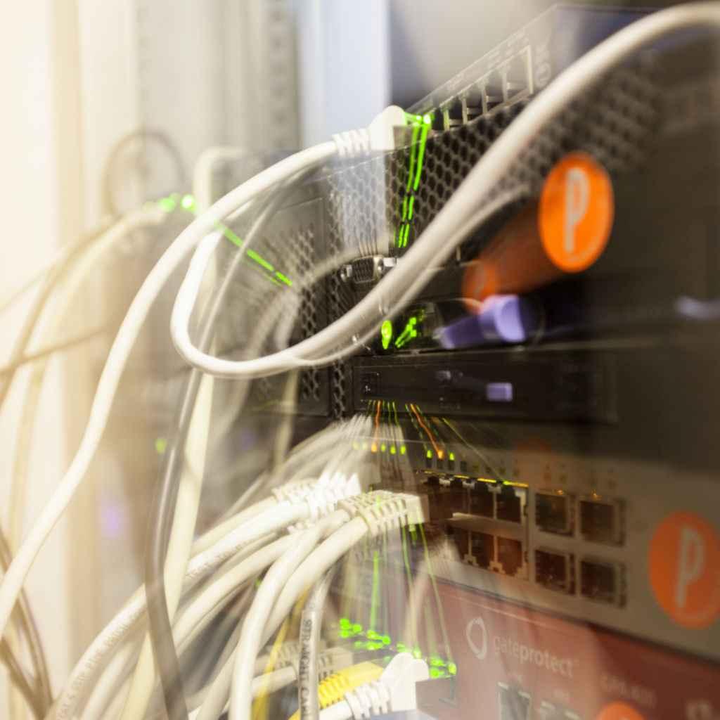 Detail eines Server-Racks mit Patch-Panel, Netzwerk-Geräten, Kabeln