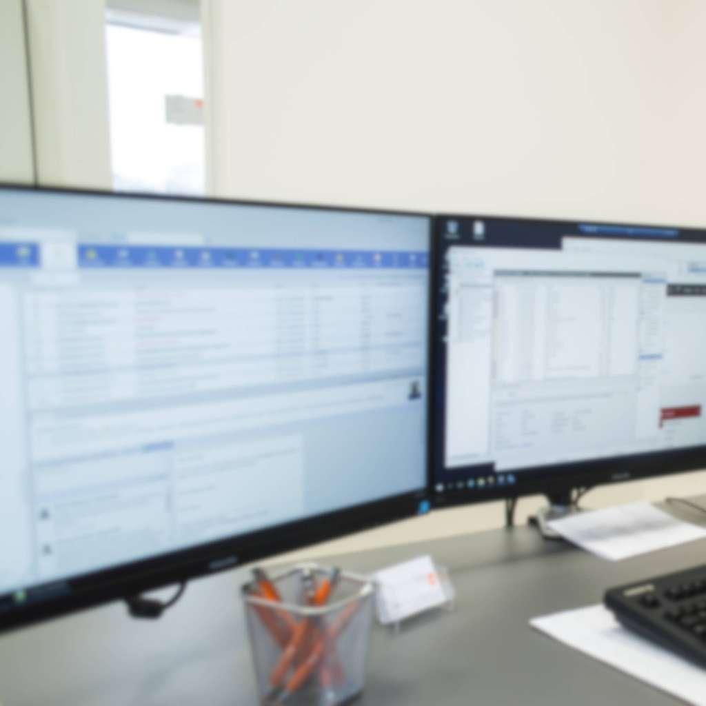 Ein Schreibtisch mit mehreren Computer-Monitoren, künstlerisch unscharf